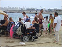 Photo of a group of people on the beach including wheelchair users