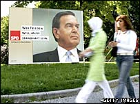 Pedestrians pass election campaign billboards featuring Gerhard Schroeder