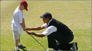Tiger Woods helps a young golfer