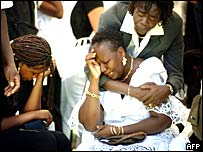 Relatives of plane crash victims cry during a memorial service in Martinique