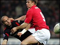 Toulouse fly-half Freddie Michalak is tackled by Scarlets scrum-half Dwayne Peel