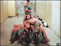 Charles Graner standing behind a pyramid of naked Iraqi prisoners at Abu Ghraib (Picture courtesy of The New Yorker)