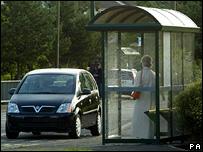 Black car at bus stop