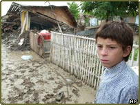 A boy standing at the gate of a destroyed house in Ivesti, Romania