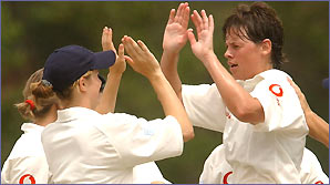 England's women's cricketers celebrate taking a wicket