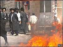 Ultra-orthodox Jewish men in Jerusalem by a fire set alight in the street