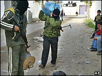 Militants in Gaza prepare a roadside bomb