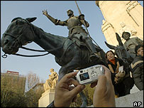 Foreign tourists take photos by statues of Don Quixote and Sancho Panza in Madrid