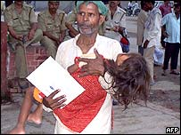 Man carries a young girl suffering from encephalitis into a hospital in Gorakhpur