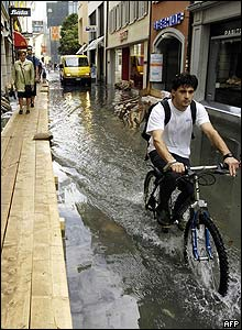 A man rides a bike through flooded Lucerne
