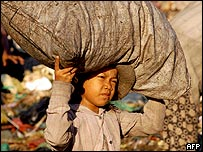 A Cambodian child scavenges at a rubbish dump