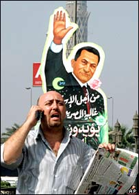 Egyptian on his mobile passes giant billboard of Hosni Mubarak