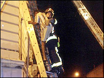 A fireman evacuates a resident from the blazing building in Paris