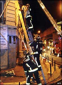 Firefighter rescues a person from the blazing apartment block in Paris
