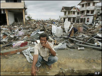 An Acehnese man squats in front of houses destroyed by tsunami Monday, Jan. 17, 2005