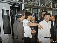 Thai Prime Minister Thaksin Shinawatra inspects the scene of the collision