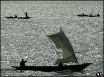 Traditional fishing vessels silhouetted against grey ocean