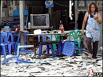 An unidentified woman dials her mobile phone following a bomb blast inside her restaurant in Thailand's troubled Yala province, 20 August 2005.