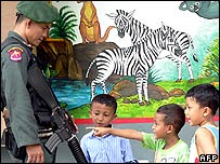 Thai children show interest in the weapon of a soldier at a polling station set up in a school during local administration elections in Thailand's troubled southern Narathiwat province, 31 July 2005
