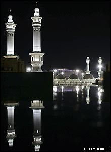 The Grand Mosque in Mecca, illuminated at night and reflected on a marble surface