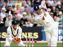 Andrew Flintoff drives as Adam Gilchrist looks on