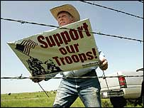 A Bush supporter places a Support our Troops sign on a fence in Texas