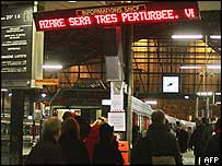 People wait for their trains at the Saint-Lazare train station in Paris, as an information panel informs that the traffic will be very perturb