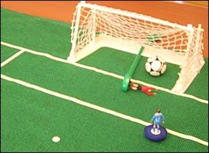 Subbuteo figure scoring a goal