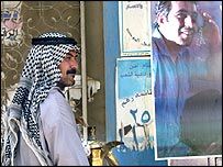 An Arabic coffee seller walks past a poster promoting the constitution in Karada, central Baghdad