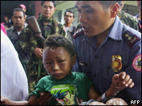A police officer carries a wounded child