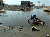 A tsunami disaster survivor tries to dig out his motorbike from a flooded street in Banda Aceh, 19 January 2005.