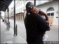 Un hombre lleva a su hija en brazos en una de las des�rticas calles de Nueva Orleans.