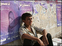 Young Iraqi street vendor rests next to a wall covered by posters promoting a referendum on the constitution, in Baghdad