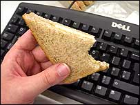 Sandwich being eaten in front of a keyboard