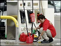 A man fills up his petrol cans ahead of Hurricane Katrina