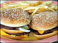 Two hamburgers and a plate of potato chips