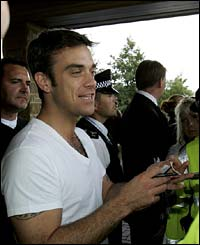 Robbie Williams signs some autographs