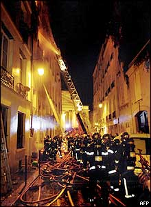 Firefighters fill the narrow Paris street