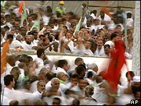 Pilgrims throw stones at pillars in Mina