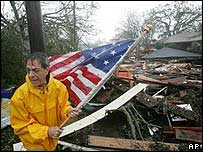 A man recovers a US flag from the rubble of his home in Gulfport, Mississippi