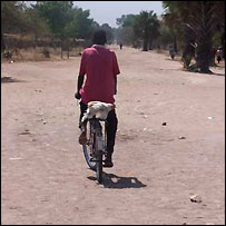 Man riding along a dusty road in Rumbek, Sudan