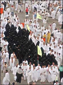 Female pilgrims are guarded by men after throwing pebbles at pillars in Mina, outside Mecca, Saudi Arabia