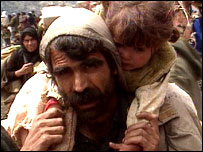 Kurdish refugee carries child