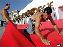Workers install the red carpet in front of the palace where the 62nd Venice Film Festival will take place