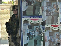 A US soldier stands by election posters in Iraq