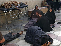 Iraqis grieve next to the bodies of their dead relatives after the bomb attack at a mosque in Baghdad