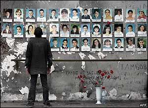 A man looks at pictures of dead schoolchildren, in Beslan, Russia