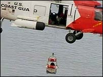 A survivor is airlifted by a US Coast Guard helicopter