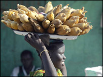 Sudanese woman carries maize to market, AFP