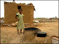 An Eritrean girl stands behind an old stove and in front of a small building housing her mother's improved mogogo